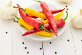 stock photo of chillies  - Chilli peppers garlic and pepper on a wooden table - JPG