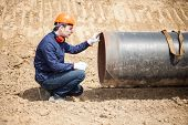 stock photo of pipe-welding  - Man examining a pipe in a construction site - JPG
