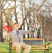 Senior holding flowers and taking selfie in park shot with tilt and shift lens