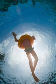 Underwater photo of a little girl swimming with inflatable ring in pool