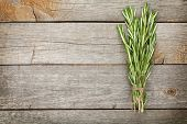 Rosemary bunch on wooden table background with copy space