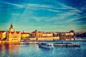 Vintage retro hipster style travel image of Vltava river with tourist boats and Prague Stare Mesto e
