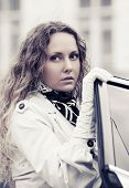 Sad beautiful woman at the car