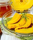 Pumpkin baked in glass pan with honey on board