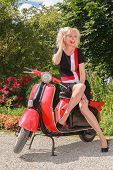 Laughing woman posing in fashionable summer dress on a scooter