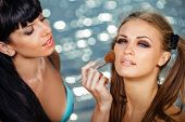 Make-up artist applying rouge on model's cheek, outdoor at summer beach