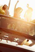 Three Women Dancing In Back Of Open Top Car