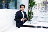 Elegant young businessman button his suit jacket
