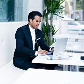 Businessman working at the notebook computer with headphones, people using modern devises for work
