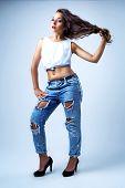 beautiful young brunette model wearing torn jeans, studio shot