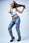 beautiful young brunette model wearing jeans, studio shot