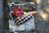 Bicycle with picnic snack in wooden box on old wooden door background