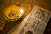 Indian classic lamp and currency notes. Hard cash is worshiped during Diwali puja.