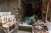 BALI, INDONESIA - SEPTEMBER 20, 2014: A trader waits for customers at his shop selling handicrafts and souvenir items made from natural resources from his village.