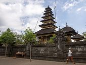 BALI, INDONESIA - SEPTEMBER 20,2014: A Hindu devotee walks past a pagoda with hands clasped and praying at the Besakih Temple Complex. This is the largest and most important Hindu temple in Bali.