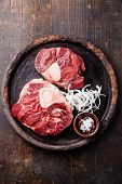 Raw Fresh Cross Cut Veal Shank And Ingredients For Making Osso Buco On Dark Wooden Background
