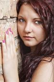 stock photo of wench  - View portrait of a young girl on a stone wall - JPG