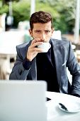 Serious and confident man drinking coffee sitting in cafe