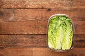 romaine lettuce heart leaves packed in a plastic container against rustic barn wood table