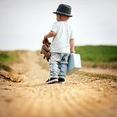stock photo of teddy  - Rear view of little boy walking on the footpath in field with suitacase and teddy bear - JPG