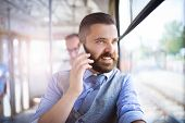 picture of handsome  - Handsome hipster modern man calling by mobile phone in tram - JPG