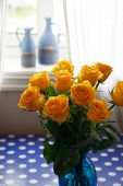 Fresh and beautiful bouquet of golden roses in a vase, by the window