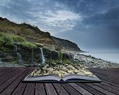 Landscape Image Of Wide Waterfall Flowing Onto Rocky Beach At Sunrise Conceptual Book Image