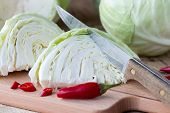 picture of cruciferous  - Cutted cabbage on cutting board with red chili peppers and knife on wooden background - JPG