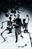 Posing Woman In Torn Pantyhose With Skeletons