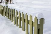 Fresh snow from a heavy snowfall covering a picket fence and sidewalk.