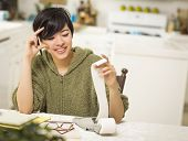 Multi-ethnic Young Woman Relieved and Smiling Over Financial Calculations in Her Kitchen.
