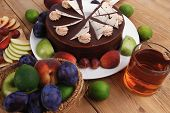 pic of brownie  - chocolate cream brownie cake layers slice topped with white chocolate and cream flowers decorated with fruits apple plum and grape on plate on wooden table with big whole cake - JPG