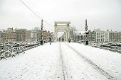 Snowy Amsterdam with the Thiny bridge in the Netherlands