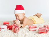 Asian baby boy with santa hat playing with Christmas present on floor.