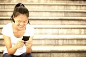 young woman use her cellphone sit on stairs