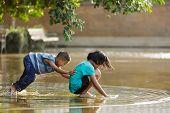BANGKOK, THAILAND, DECEMBER 25, 2011: Boy having fun pushing his sister in a flooded square in Bangkok, Thailand