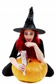 witch with bloodstained hands with a hatchet in hand sits on a pumpkin