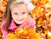 Autumn Portrait Of Cute Smiling Little Girl With Maple