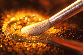 stock photo of face-powder  - Close-up on brush and gold shining powder. Focus on tip of the brush. ** Note: Shallow depth of field - JPG
