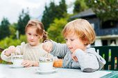 Adorable children drinking hot chocolate outdoors, spending good time on vacation in alpine mountain