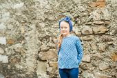 Outdoor portrait of a cute fashion little girl, wearing warm blue pullover and headband