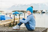 Outdoor portrait of a cute little girl resting by the lake in a small port, wearing warm blue pullov