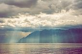 image of day judgement  - Beautiful sun rays falling through heavy clouds on the mountains and the lake - JPG
