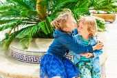 Two adorable kids on vacation, big sister giving a hug to her toddler brother