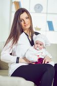 Young woman holding her baby in her arms in the living room