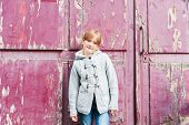 Adorable little girl in a grey jacket standing against purple door in a city