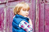 Portrait of adorable toddler boy outdoors on a street against old door