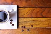 Cup Of Coffee And Beans On A Brown Wooden Table