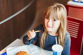 Little girl eating fast food in a cafe