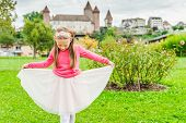 Cute little girl playing in a nice garden, dreaming to be a princess